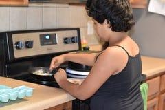 烹调早餐的中间姐妹在厨房 免版税图库摄影