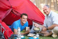 烹调早餐的父亲和成人儿子野营假日 免版税库存照片