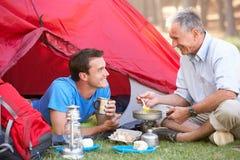 烹调早餐的父亲和成人儿子野营假日 图库摄影