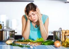 烹调晚餐的哀伤的主妇 免版税库存图片