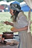 烹调晚餐的妇女reenactor 库存图片