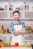 烹调晚餐的微笑的人在厨房里 库存照片
