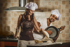 烹调晚餐的混合的族种年轻夫妇 免版税库存图片