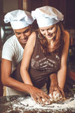 烹调晚餐的混合的族种年轻夫妇 库存图片