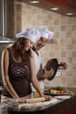 烹调晚餐的混合的族种年轻夫妇 图库摄影
