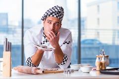烹调曲奇饼的年轻人在厨房里 免版税库存照片