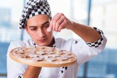 烹调曲奇饼的年轻人在厨房里 免版税库存图片