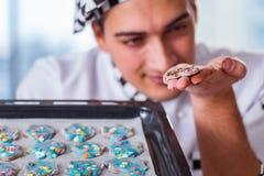 烹调曲奇饼的年轻人在厨房里 库存照片