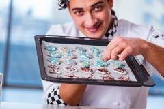 烹调曲奇饼的年轻人在厨房里 库存图片