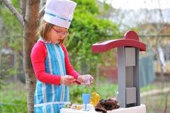 烹调有乐趣的女孩一点使用 免版税库存图片