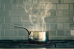 烹调有烟的罐在灰色Bricked背景 库存照片