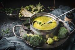烹调有绿色romanesco的罐和硬花甘蓝汤和杓子在黑暗的土气厨房用桌上 健康食物和饮食营养 图库摄影