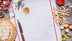 烹调未加工的剁碎的牛肉鸡蛋的概念砍了葱刀子调味料浆糊在白色餐巾的西红柿酱在木backgroun 免版税库存照片