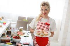 烹调杯形蛋糕的微笑的白肤金发的妇女在厨房里 库存图片