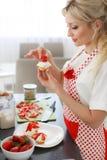 烹调杯形蛋糕的微笑的白肤金发的妇女在厨房里 库存照片