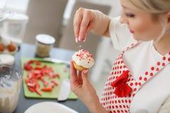 烹调杯形蛋糕的微笑的白肤金发的妇女在厨房里 免版税库存图片