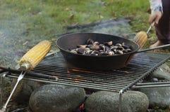 烹调栗子和棒子在火 免版税库存照片
