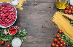 烹调概念、未加工的肉末、西红柿酱、西红柿、面团、巴马干酪、葱、大蒜、草本和草本的博洛涅塞面团, 免版税图库摄影