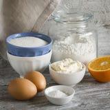 -烹调橙色蛋糕的未加工的成份-面粉,鸡蛋,黄油,糖,桔子 烘烤成份 免版税库存图片