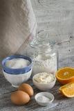 -烹调橙色蛋糕的未加工的成份-面粉,鸡蛋,黄油,糖,桔子 图库摄影