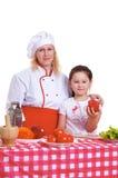 烹调正餐的母亲和女儿 免版税库存图片