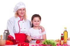 烹调正餐的母亲和女儿 图库摄影