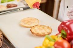 烹调汉堡的厨师在厨房 免版税库存图片