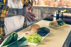 烹调汉堡的肥胖人在厨房里 免版税库存照片