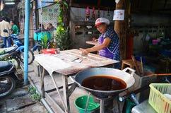 烹调油炸doughstick的老妇人 免版税库存图片