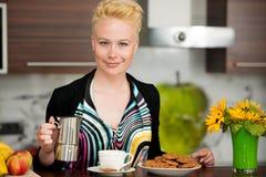 烹调浓咖啡咖啡的美丽的年轻白种人白肤金发的妇女  免版税库存图片