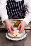 烹调烤宽面条海鲜的主厨 库存图片