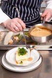 烹调烤宽面条海鲜的主厨 免版税库存照片