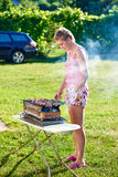 烹调烤肉的俏丽的女孩户外 免版税图库摄影