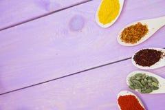 烹调热的辣食物概念 干香料、豆和草本在塑料杯子,玻璃瓶子有黄柏的和木匙子,紫色木bac 免版税库存照片