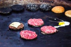 烹调牛肉和猪肉小馅饼用鸡蛋和乳酪汉堡的 肉在火在格栅的烤肉kebabs烤了 烤汉堡裁减 免版税图库摄影