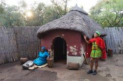烹调玉米膳食的非洲妇女在部族房子在Lesedi别墅 免版税库存照片
