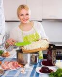 烹调用肉和圆白菜的主妇 免版税库存图片