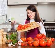 烹调用蕃茄的微笑的妇女 库存图片