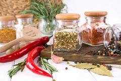 烹调的产品在厨房里,厨房器物,草本,在玻璃瓶子的五颜六色的干香料在白色桌上 图库摄影