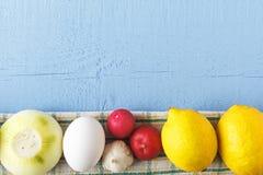 烹调的健康食物有机产品 未煮过的鸡蛋和成熟葱,大蒜,柠檬,在木背景的萝卜 与c的顶视图 免版税库存图片