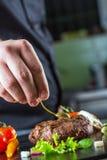烹调的厨师在旅馆或餐馆厨房里,仅手 与菜装饰的准备的牛排 免版税库存照片