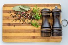 烹调的各种各样的盘和沙拉香料在切板 图库摄影