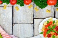烹调的意大利面团- farfalle、蕃茄、胡椒和蓬蒿成份在老木背景 与空间的顶视图te的 免版税库存图片