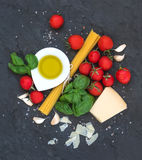 烹调的意大利面食成份 意粉、橄榄油、大蒜、帕尔马干酪、蕃茄和新鲜的蓬蒿在黑板岩 免版税库存照片