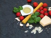 烹调的意大利面食成份 意粉、橄榄油、大蒜、帕尔马干酪、蕃茄和新鲜的蓬蒿在黑板岩 库存图片
