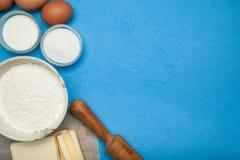 烹调的成份:糖、鸡蛋、面粉和油在蓝色背景 r 图库摄影