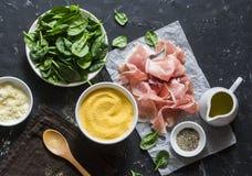 烹调的成份-麦片粥、菠菜和熏火腿 在地中海样式的可口午餐 在黑暗的背景,上面竞争 免版税库存图片