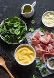烹调的成份-麦片粥、菠菜和熏火腿 在地中海样式的可口午餐 在黑暗的背景,上面竞争 免版税库存照片
