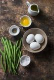 烹调的早餐或快餐-鸡蛋,青豆,橄榄油,在木背景,顶视图的香料未加工的成份 免版税图库摄影