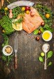 烹调的未加工的三文鱼准备在与新鲜的成份、叉子和匙子,顶视图的土气木背景 免版税库存照片